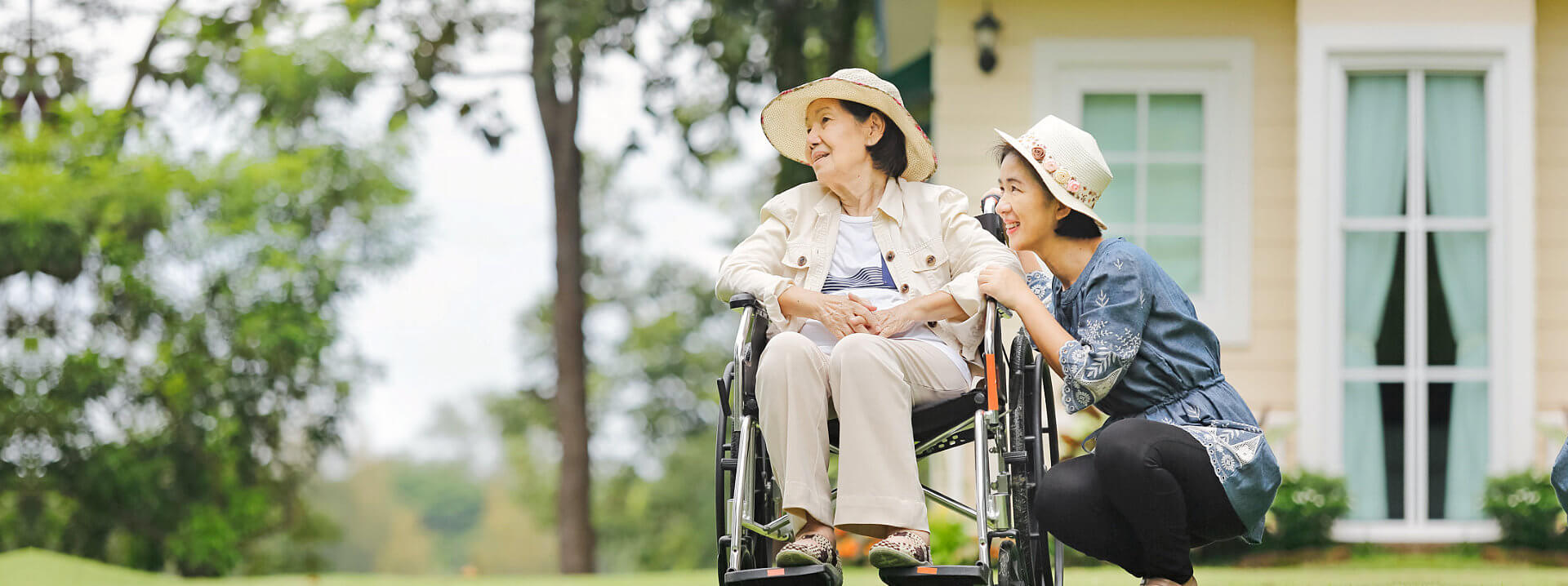 Elderly women relax on wheelchair in backyard with daughter