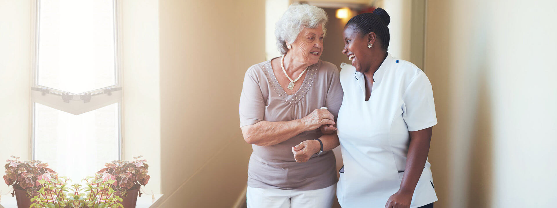 Portrait of happy female caregiver and senior women walking together at home